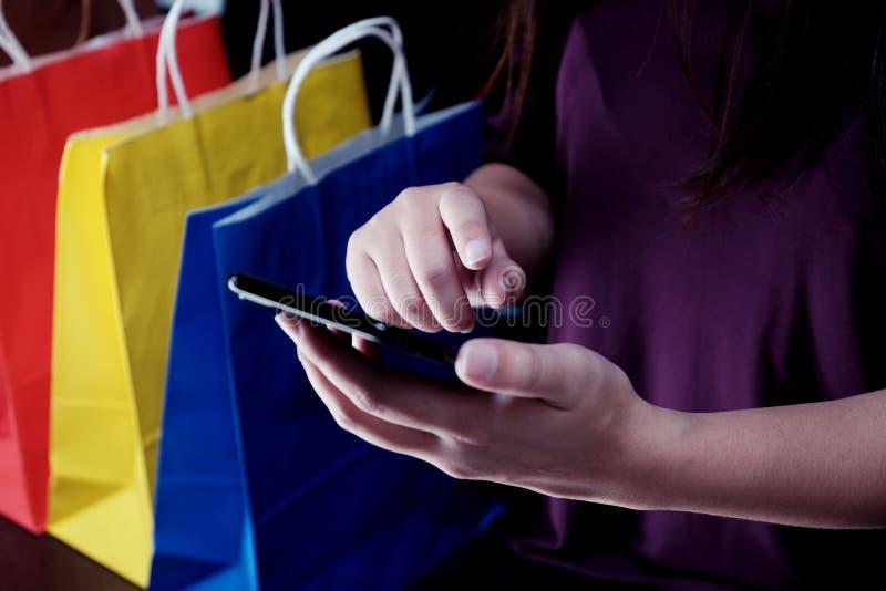 Aziatische meisjes die verkoop het winkelen zakken houden het concept van de consumentismelevensstijl in het van de de bewaarcelt stock fotografie
