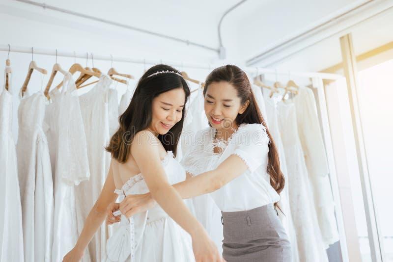 Aziatische meisjesbruid die op huwelijkskleding proberen, Vrouwenontwerper die aanpassing met het meten van band maken stock foto's
