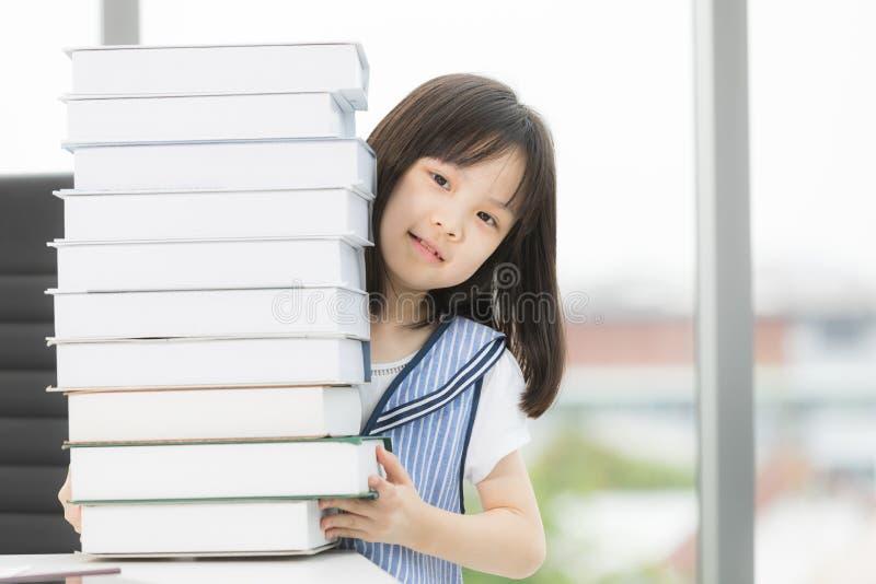 Aziatische meisjesglimlachen aan camera, zij zitting bij lijst stock foto's