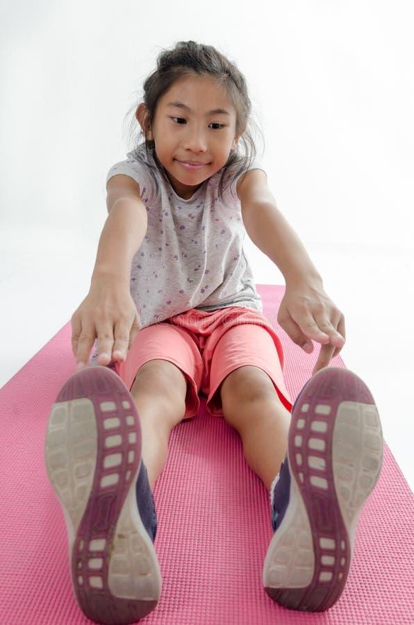 Aziatische meisjesoefening op roze yogamat royalty-vrije stock fotografie