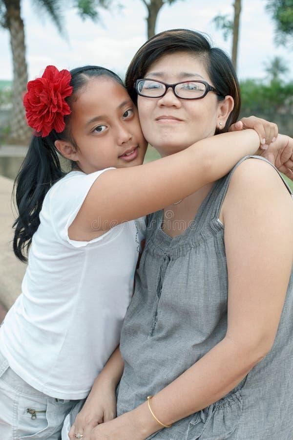 Aziatische meisjesomhelzing op moeder stock afbeeldingen