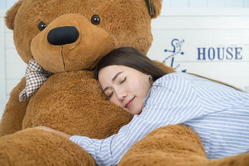 Aziatische meisjesslaap op het bed met een grote bruine teddybeer stock afbeeldingen