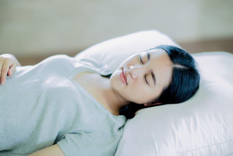 Aziatische meisjesslaap op het witte bed stock afbeeldingen