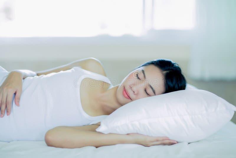 Aziatische meisjesslaap op het witte bed stock afbeelding