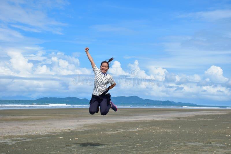 Aziatische meisjessprongen op het strand royalty-vrije stock fotografie