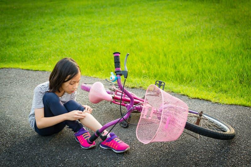Aziatische meisjezitting neer op de weg met een beenpijn toe te schrijven aan een fietsongeval, de fietsdaling dichtbij het kind, stock foto