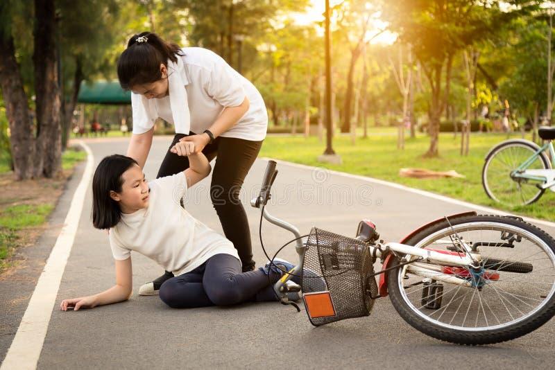 Aziatische meisjezitting neer op de weg met een beenpijn toe te schrijven aan een fietsongeval, de fietsdaling dichtbij het vrouw royalty-vrije stock afbeeldingen
