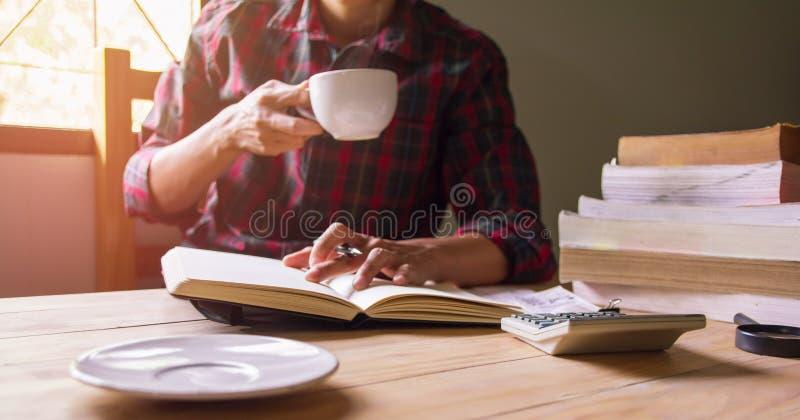 Aziatische mens in de holdingskop van het scottistoverhemd van koffie het drinken en gelezen boek royalty-vrije stock afbeeldingen