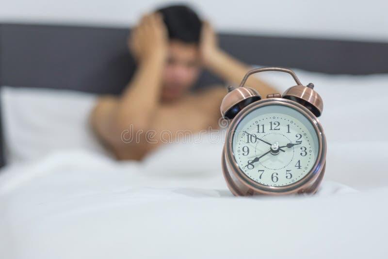 Aziatische mens die in bed laat bij nacht, jonge mannelijke slaap in slaapkamer thuis liggen slapeloosheidsslaap royalty-vrije stock foto