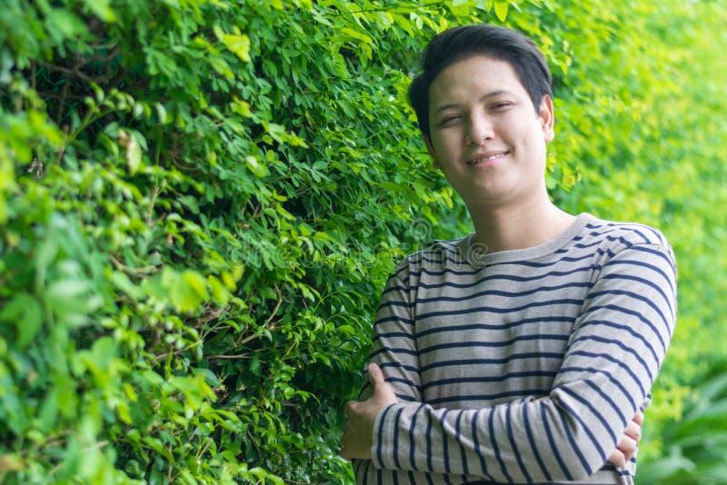 Aziatische mens die en zijn het gelukkige glimlachen bevinden zich tonen royalty-vrije stock fotografie