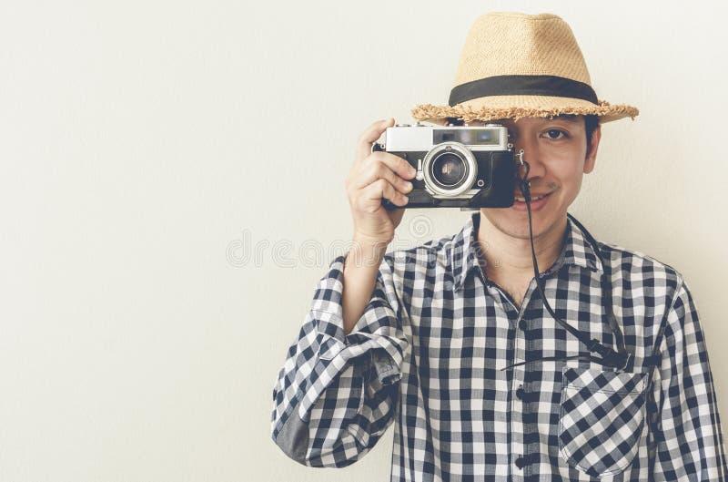Aziatische mens die foto op retro camera nemen stock fotografie