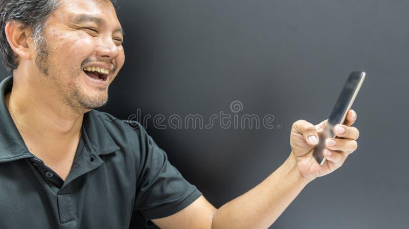 Aziatische mens die gebruikend smartphone in donkere stijl glimlachen stock foto