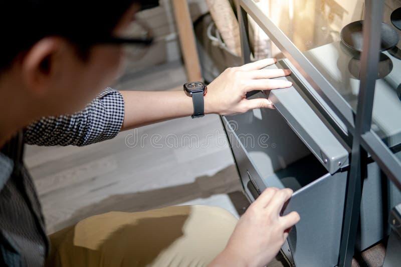 Aziatische mens die grijze doos op plank openen stock foto's