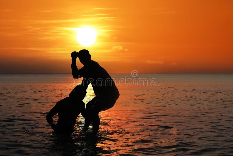 Aziatische mens die het Thaise in dozen doen op het overzeese strand uitoefenen bij zonsondergang royalty-vrije stock fotografie