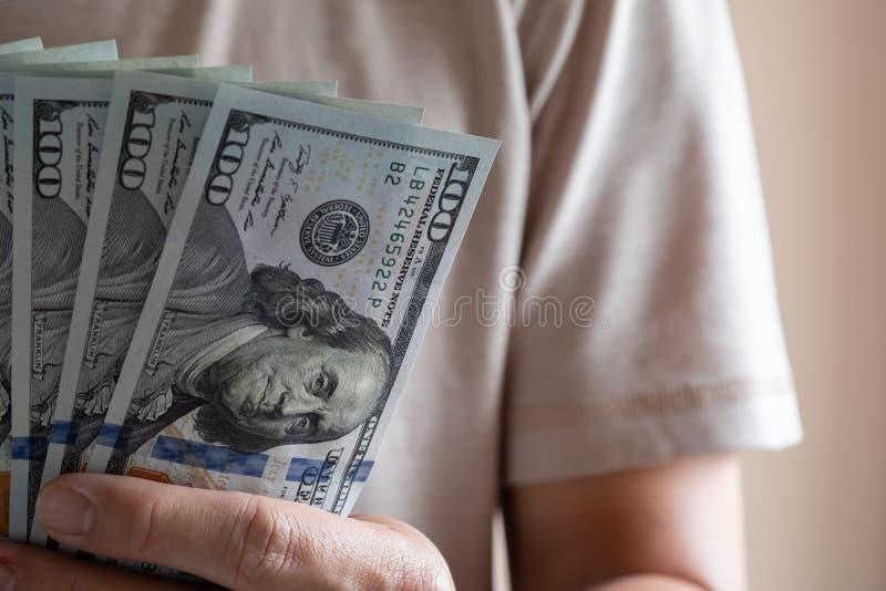 Aziatische mens die honderd dollarrekening houden Rijk en rijkdomconcept royalty-vrije stock afbeelding