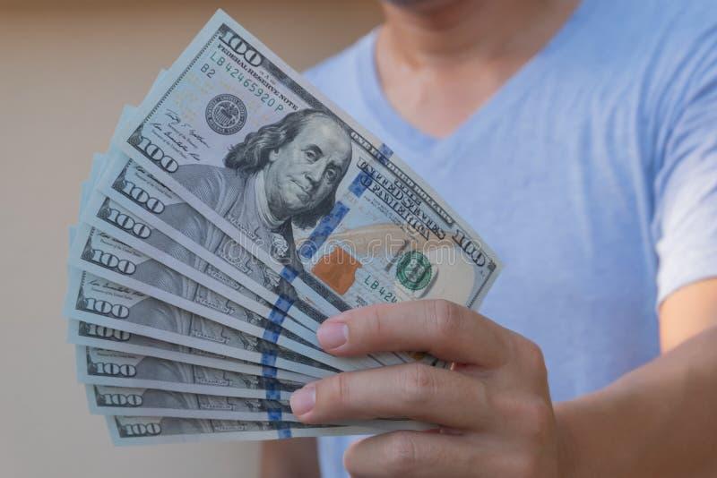 Aziatische mens die honderd dollarrekening houden Rijk en rijkdomconcept stock foto's