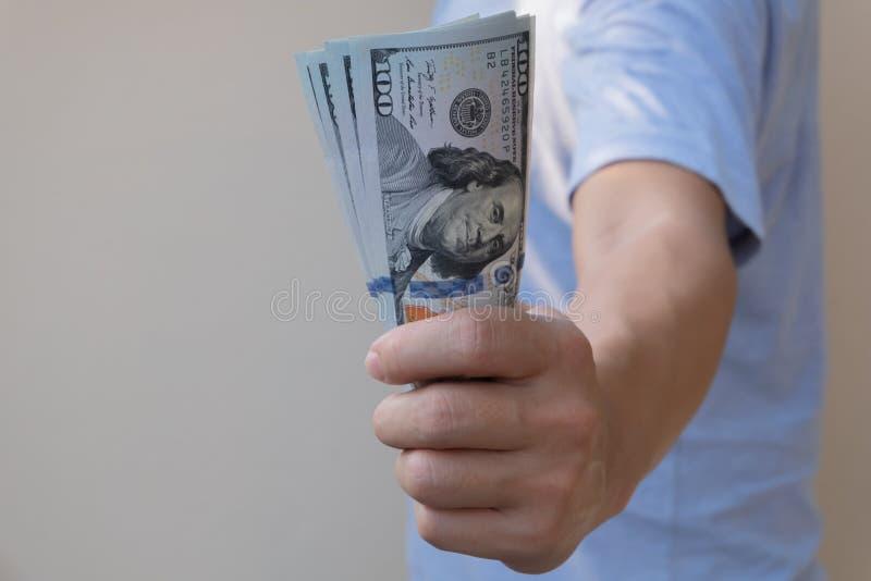 Aziatische mens die honderd dollarrekening houden Rijk en rijkdomconcept royalty-vrije stock foto's