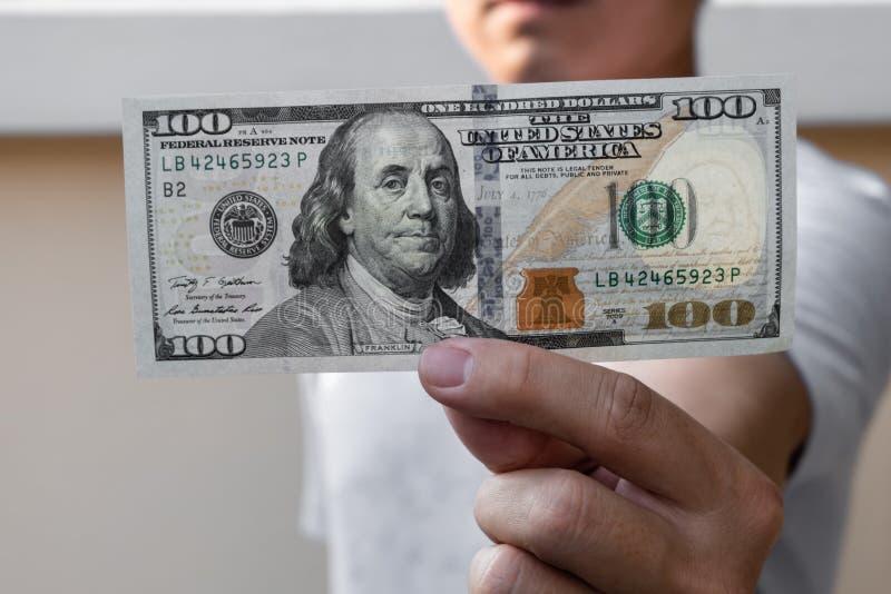 Aziatische mens die honderd dollarrekening houden Rijk en rijkdomconcept stock foto