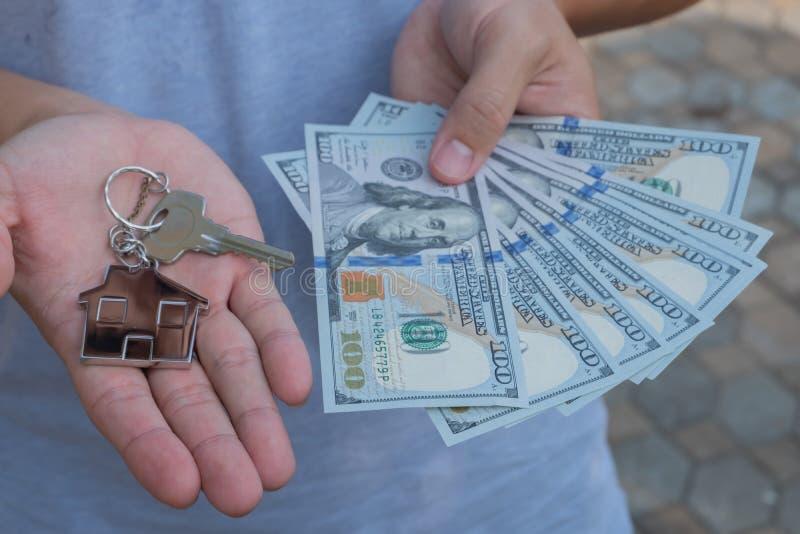 Aziatische mens die honderd dollarsrekeningen en de zeer belangrijke keten van de huisvorm houden Bezitsinvestering en het concep royalty-vrije stock afbeelding