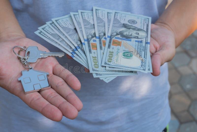 Aziatische mens die honderd dollarsrekeningen en de zeer belangrijke keten van de huisvorm houden Bezitsinvestering en het concep stock afbeeldingen