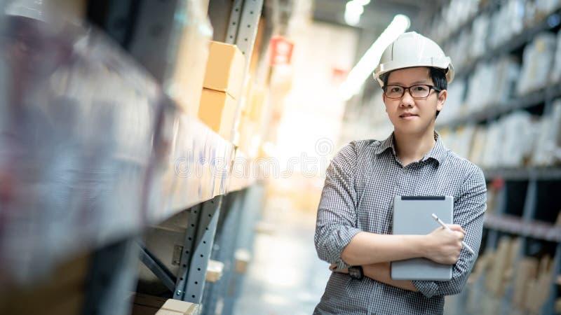 Aziatische mens die inventarisatie op tablet in pakhuis doen royalty-vrije stock fotografie