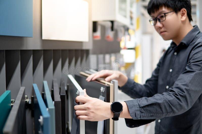 Aziatische mens die kabinet of countertop materialen kiezen royalty-vrije stock fotografie