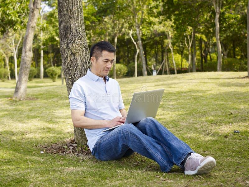 Aziatische mens die laptop in openlucht met behulp van stock afbeelding