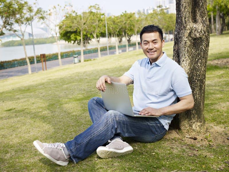 Aziatische mens die laptop in openlucht met behulp van royalty-vrije stock fotografie