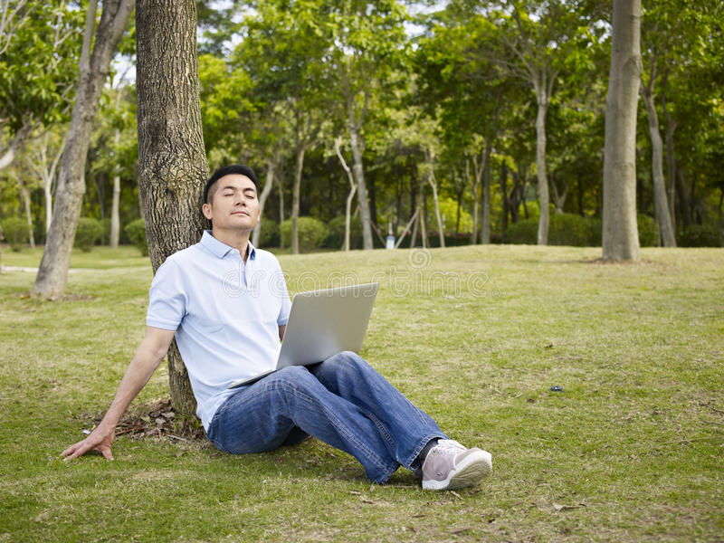 Aziatische mens die laptop in openlucht met behulp van royalty-vrije stock foto