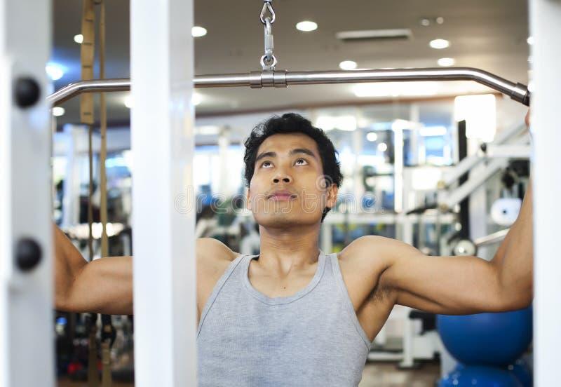 Aziatische mens die lat pulldown machine met behulp van stock afbeelding