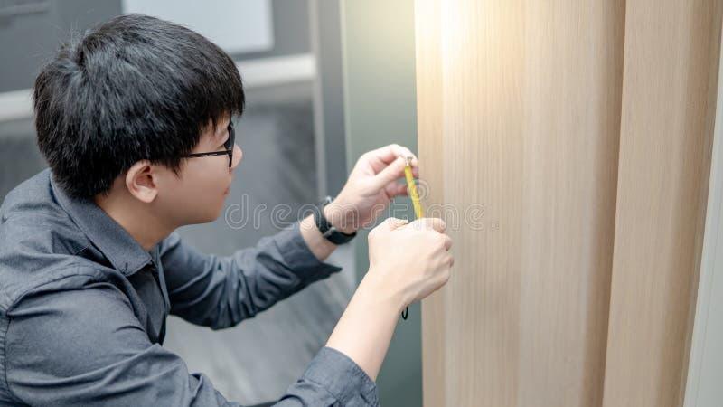 Aziatische mens die meetlint op kabinetsmaterialen gebruiken stock fotografie