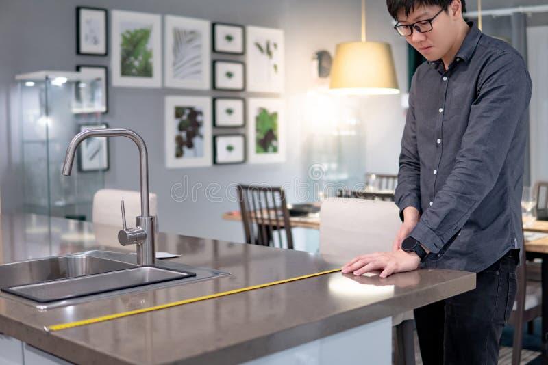 Aziatische mens die meetlint op keukenteller gebruiken royalty-vrije stock foto's