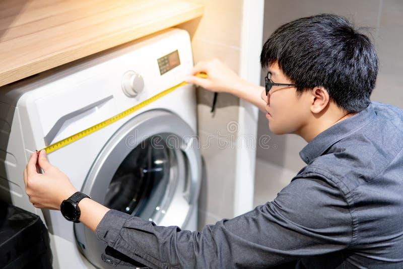 Aziatische mens die meetlint op wasmachine gebruiken stock foto