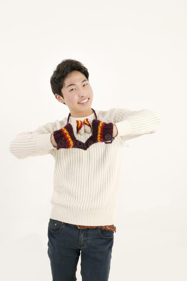 Aziatische mens die met bonthandschoen hartvorm maakt royalty-vrije stock foto's
