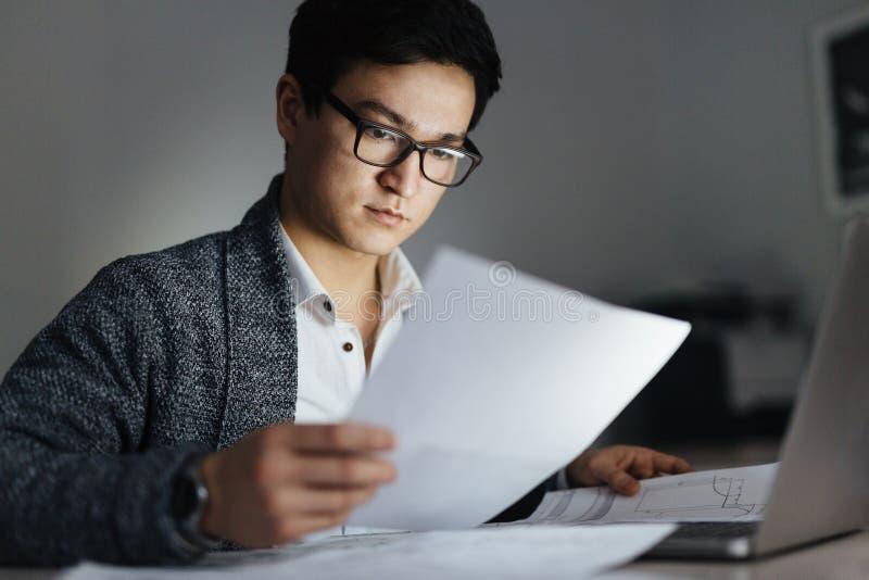 Aziatische Mens die met Documenten bij Nacht werken stock foto