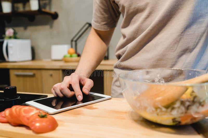 Aziatische mens die recept op digitale tablet en kokend gezond voedsel in de huiskeuken op een zonnige dag kijken stock afbeeldingen