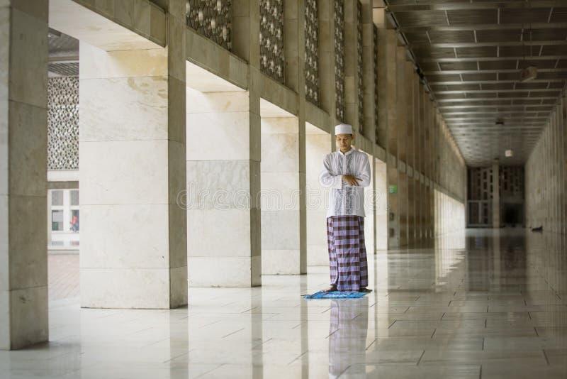 Aziatische mens die Salat op de Istiqlal-moskee doen stock fotografie