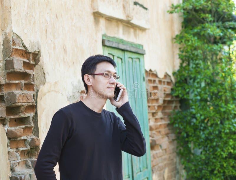 Aziatische mens die smartphone outsite in oude stad gebruiken royalty-vrije stock foto's