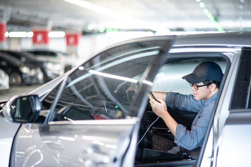 Aziatische mens die smartphonezitting in de auto gebruiken stock afbeelding