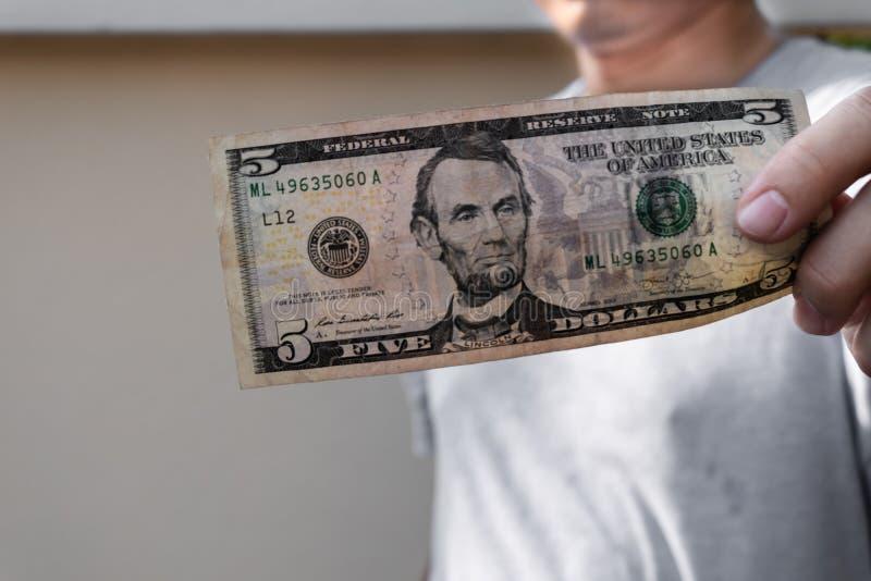 Aziatische mens die vijf dollarrekening houden Rijk en rijkdomconcept stock foto