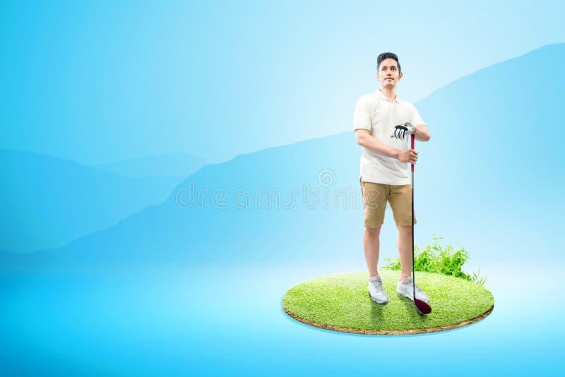 Aziatische mens die zich met een houten golfclub bevinden stock afbeeldingen