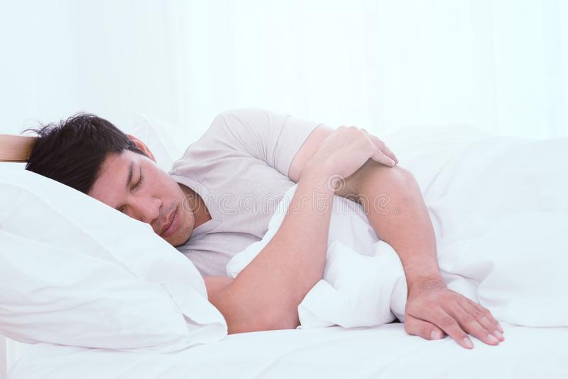 Aziatische mens die zijmanier op wit bed slapen stock foto