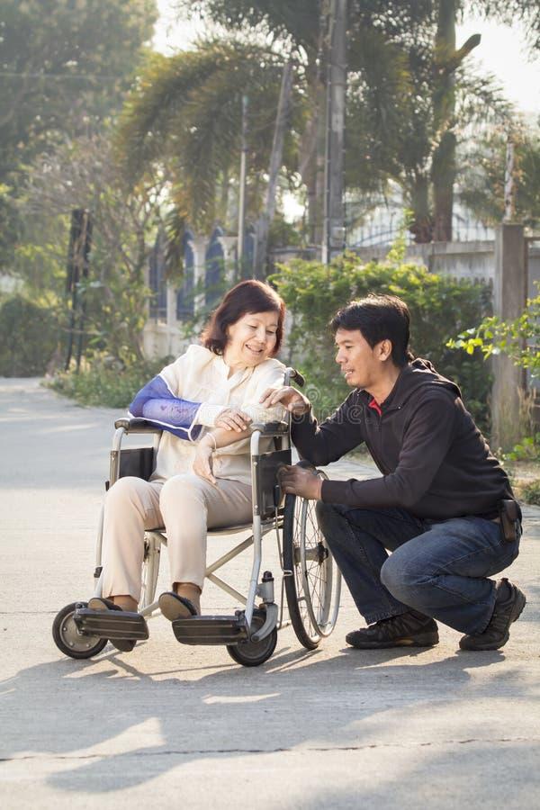 Aziatische mens die zijn bejaarde moeder voor een gang nemen royalty-vrije stock afbeelding