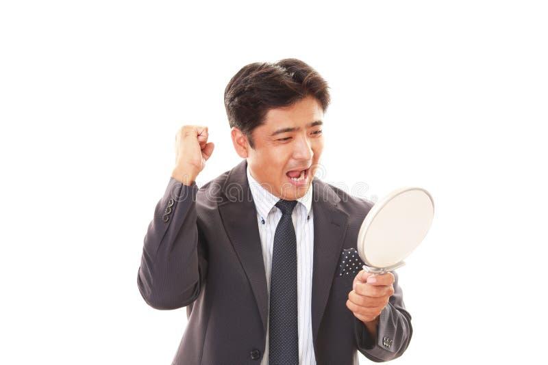 Aziatische mens die zijn haar in spiegel bekijken royalty-vrije stock foto