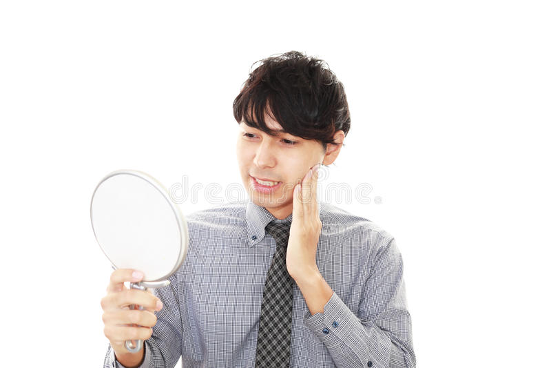 Aziatische mens die zijn haar in spiegel bekijken royalty-vrije stock afbeeldingen