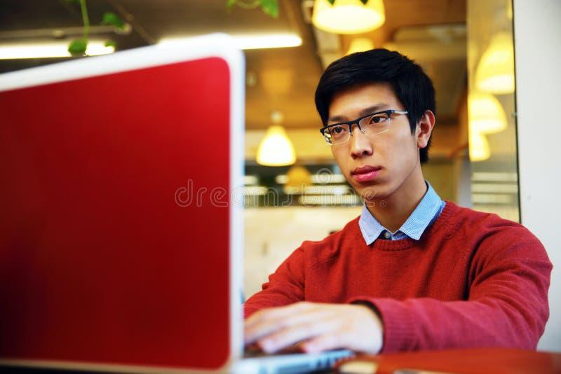 Aziatische mens in glazen die aan laptop werken stock foto's
