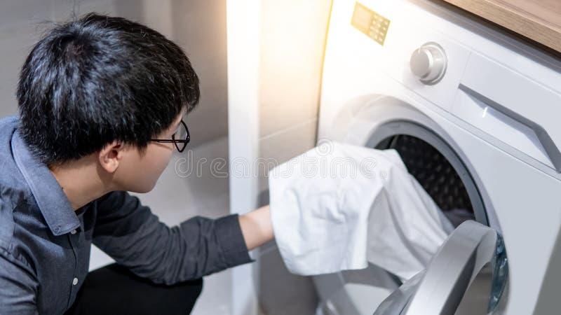 Aziatische mens het plukken kleren van wasmachine stock foto