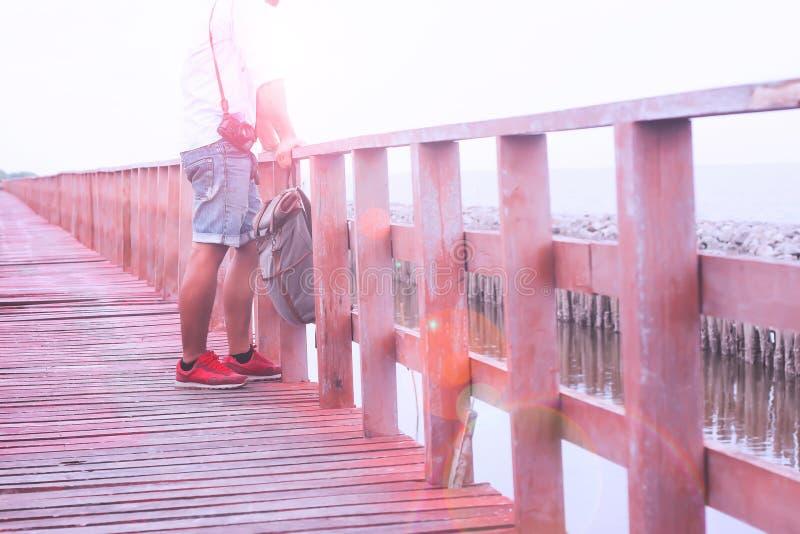 Aziatische mens met camera en zak die zich op houten brug bevinden die rond strand en zand, de Zomerreis zien stock afbeelding