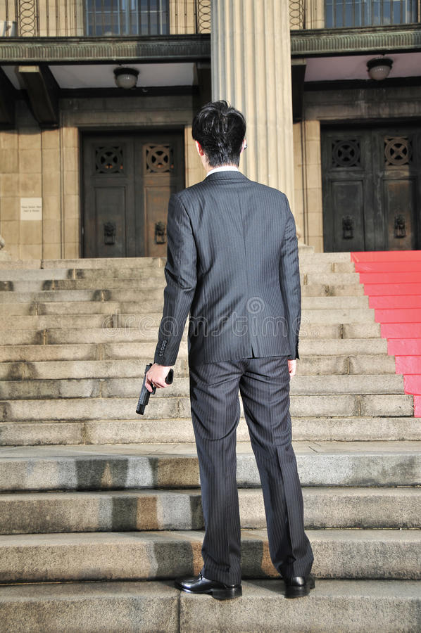 Aziatische Mens met een Kanon met rug die kijker 2 onder ogen ziet stock fotografie