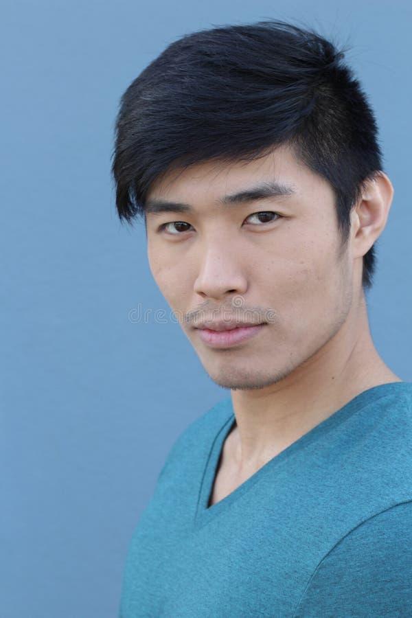Aziatische mens met ernstige uitdrukking over blauwe achtergrond stock afbeelding